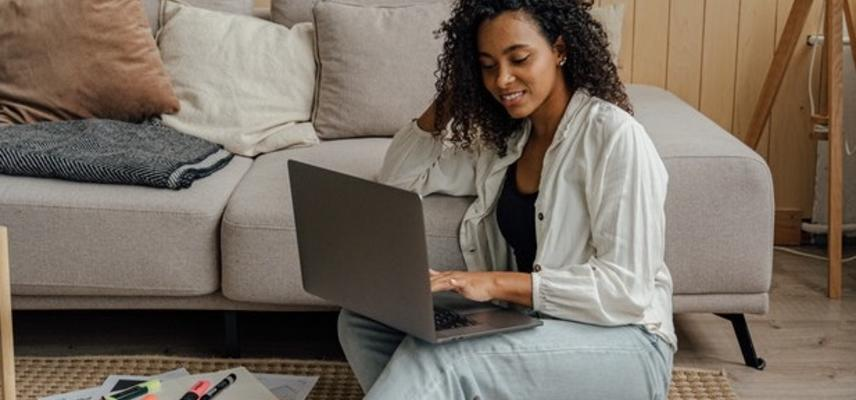 Woman in robe sitting next to couch using macbook