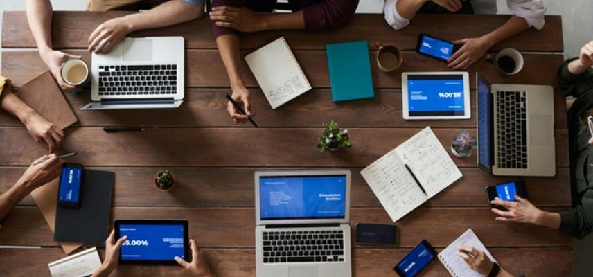 Stock photo of people and laptops around a table